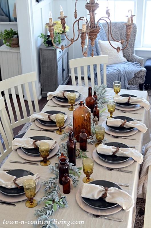Linen pom pom napkins and vintage amber bottles at a table setting