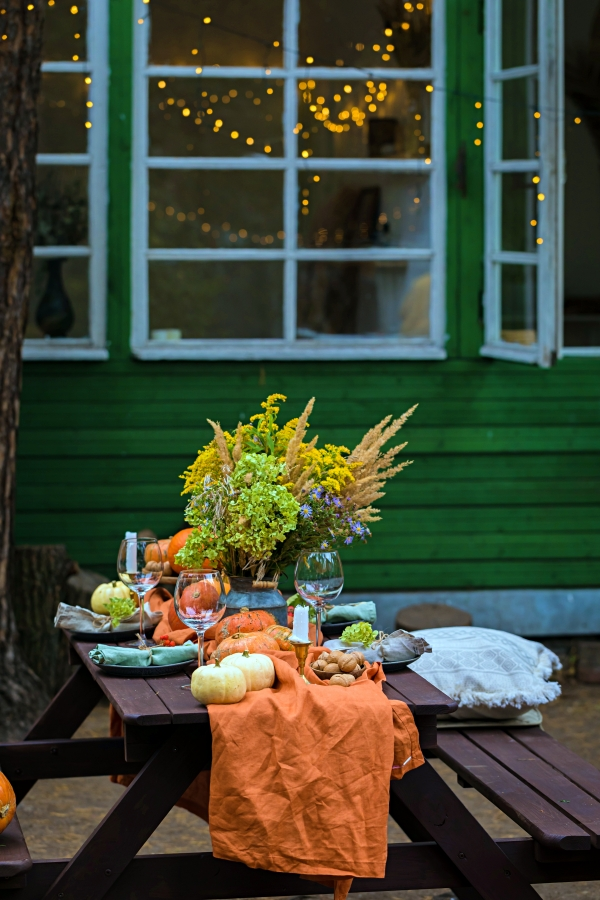 Fall themed holiday table setting arrangement for a seasonal party, glasses, pumpkins, candles, field flowers