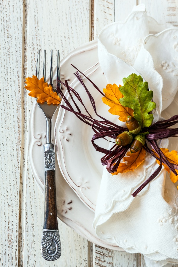 Autumn table setting with white dishes, silk leaves, and raffia