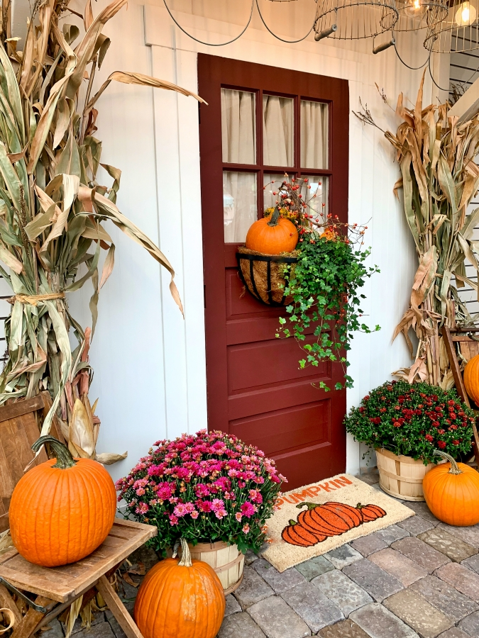 Mums, pumpkins, and cornstalks create the perfect fall porch decor