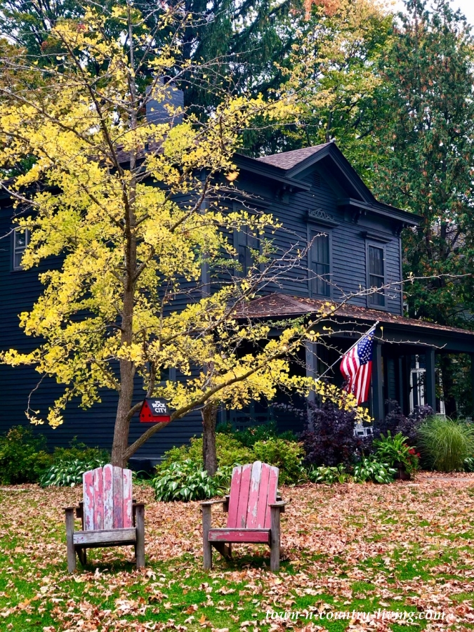 Black Clapboard Victorian House with Red Adirondack Chairs