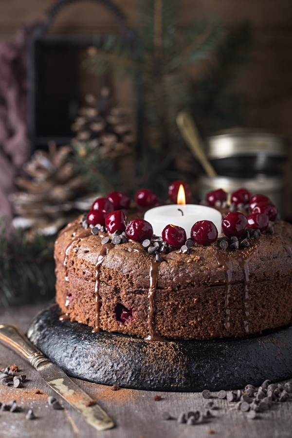 Double chocolate cherry cake with spices and big candle in center of cake ring
