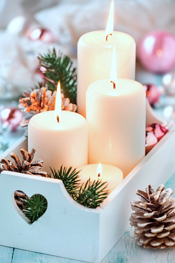 Festive Christmas decoration with four Advent candles in a white shabby chic tray with fit branches, pine cones.