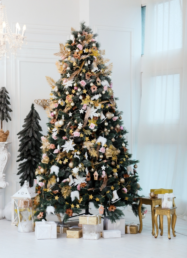 White faux poinsettias and golden ferns create a botanical style Christmas tree