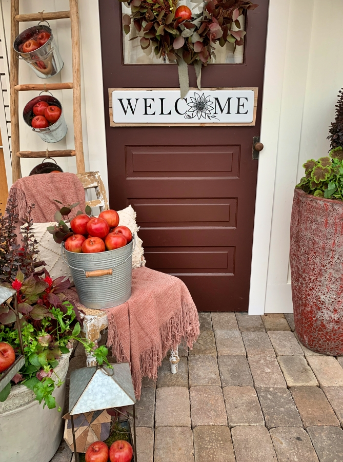 Country porch decorated for autumn season.  Welcome sign on wooden front door