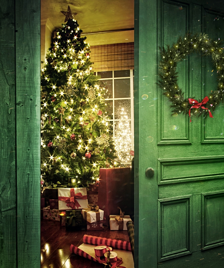 Rustic door opening into a room with Christmas tree