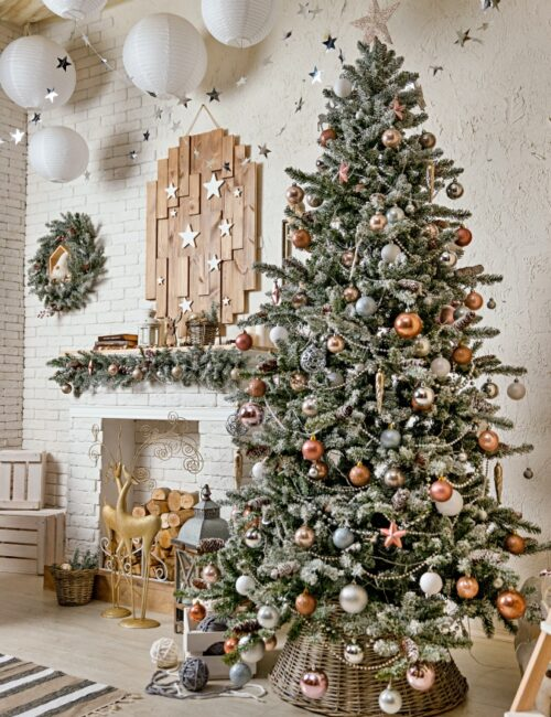 The Scandinavian style Christmas or New Year background: big Christmas tree by the fireplace, pink glass balls and toys, wooden decoration, wool blanket, floor lamp, graceful Golden deer