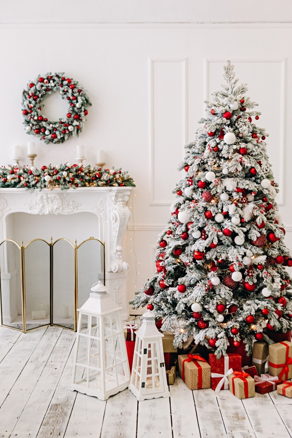 Red and White Christmas Tree Next to  Fireplace Mantel