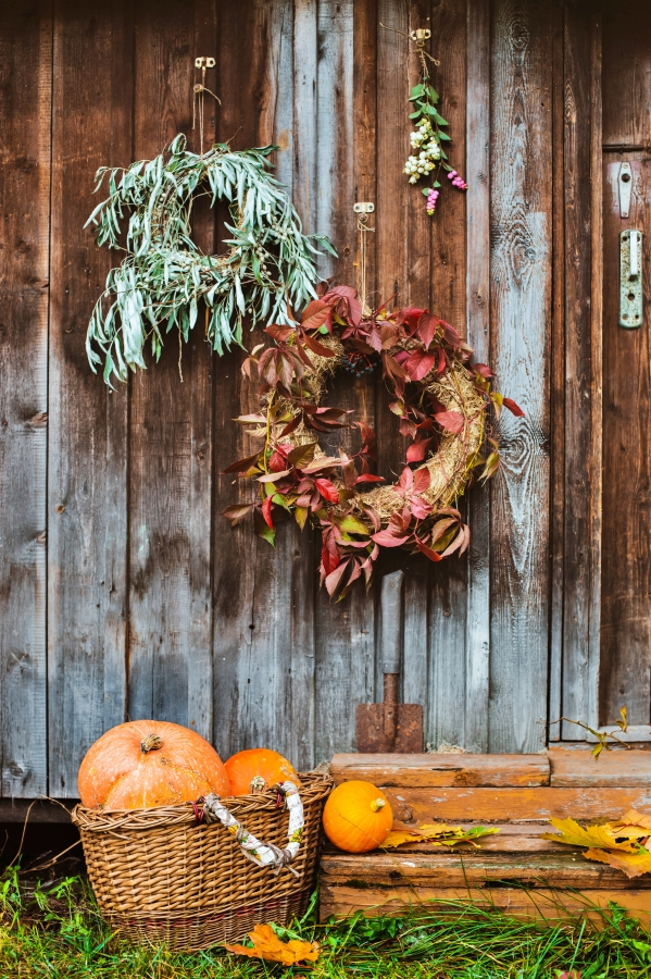 Fall front porch. autumn wreath and pumpkins on old wooden rustic background