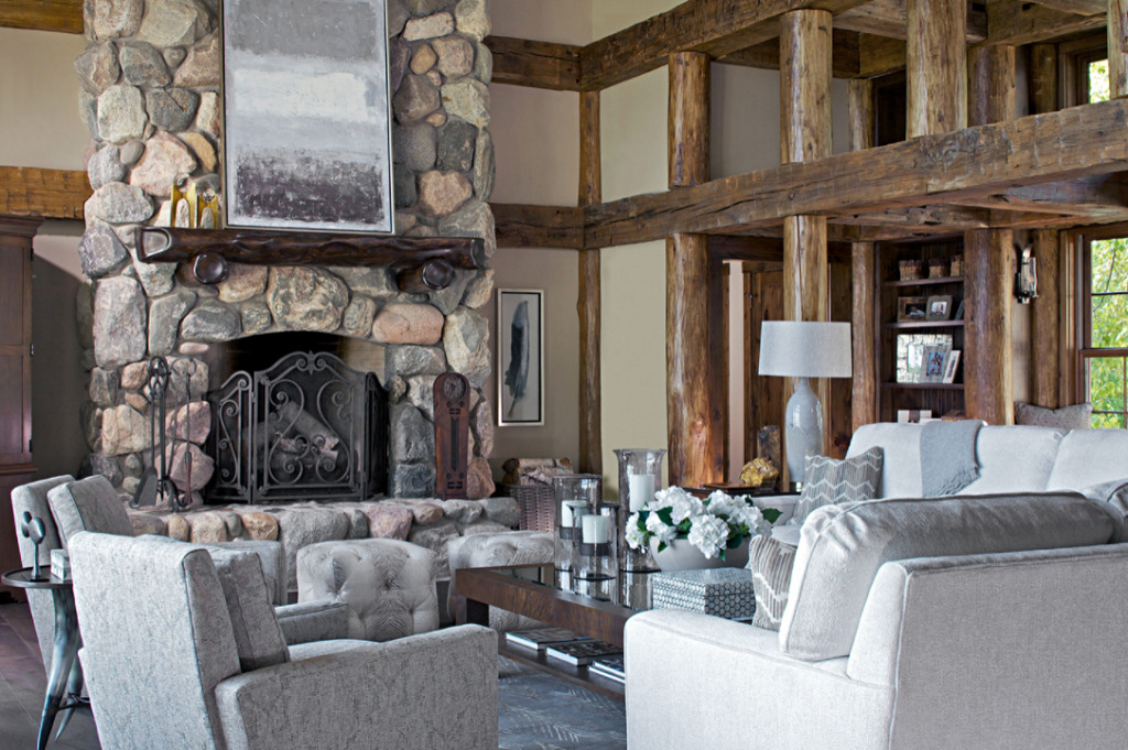 Large stone fireplace in cabin style living room decorated in neutral earth tones