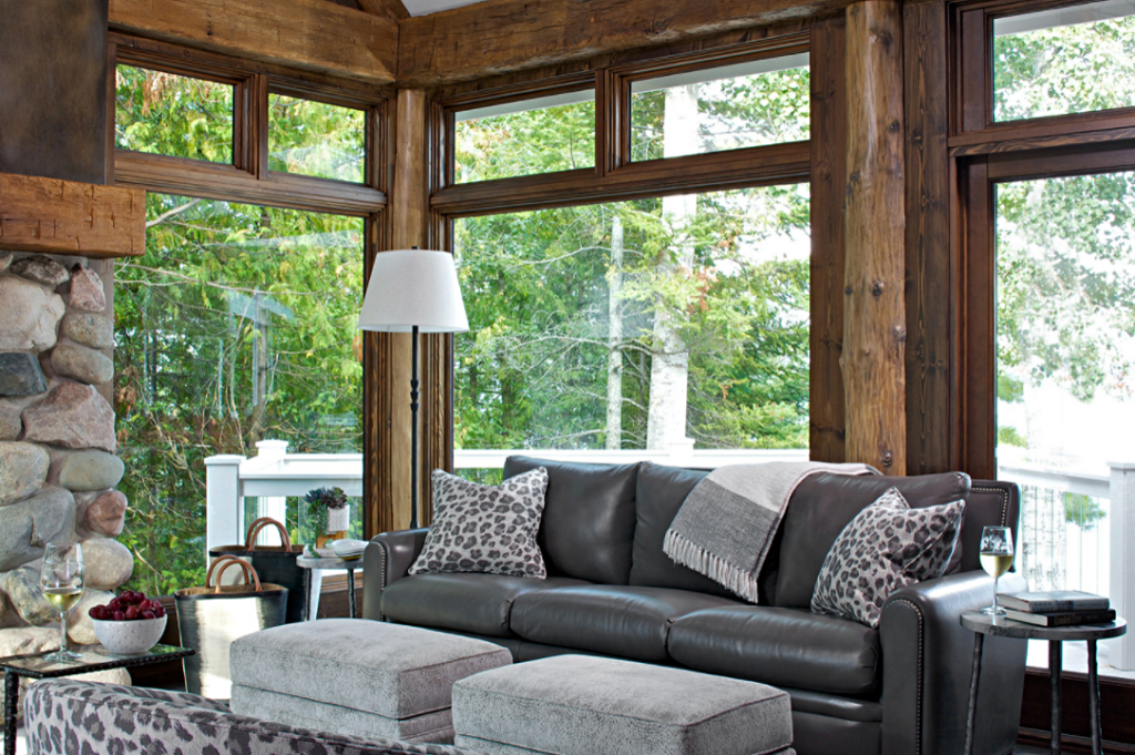 Cabin style living room with expansive windows framed with logs