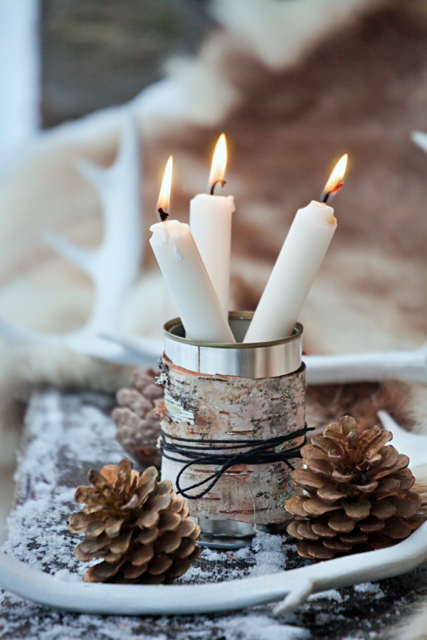 Three white candles in tin can covered in birch bark