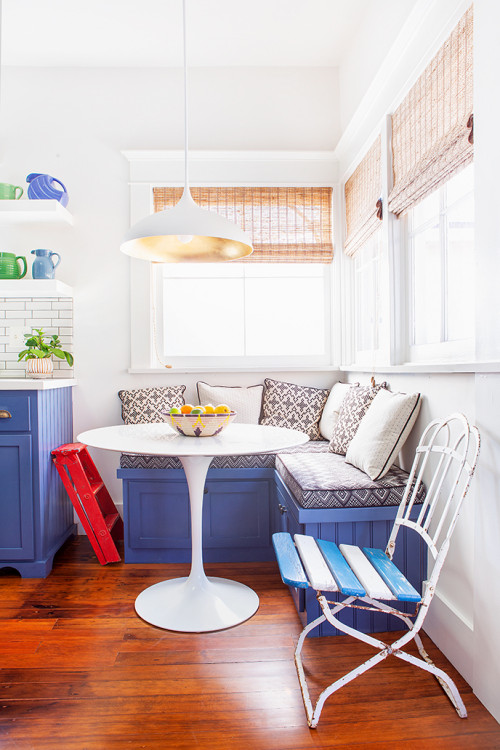 Charming blue and white breakfast nook with banquette and corner windows