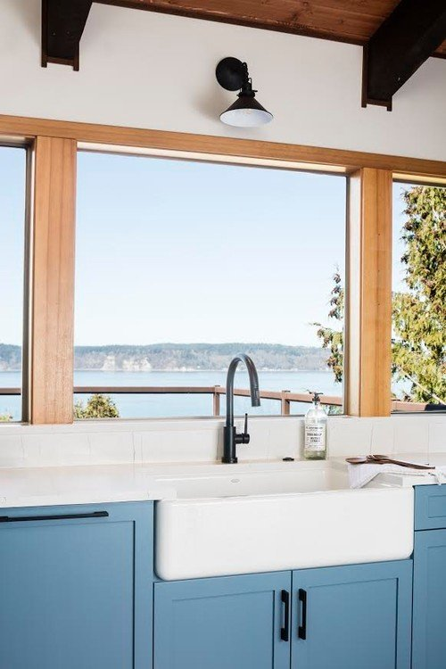 White farmhouse sink with large windows in peaceful blue kitchen