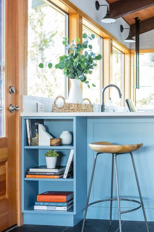 Light blue kitchen cabinetry with built-in shelving at the peninsula