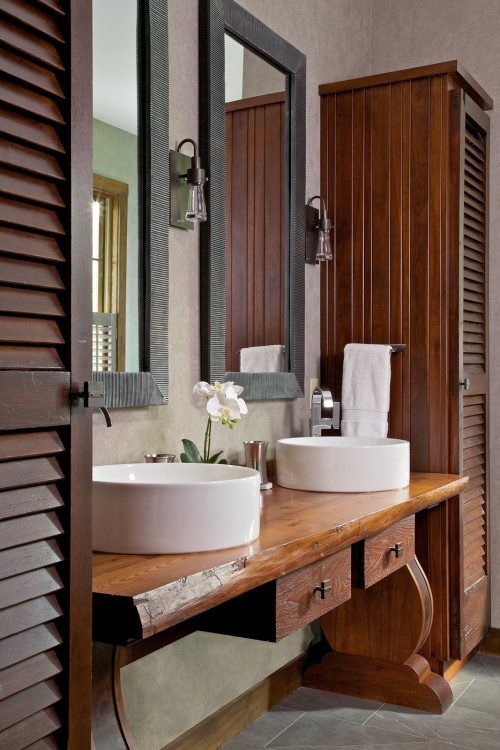 Double sink bathroom with wood cabinetry, louvered doors, and gray slate tile