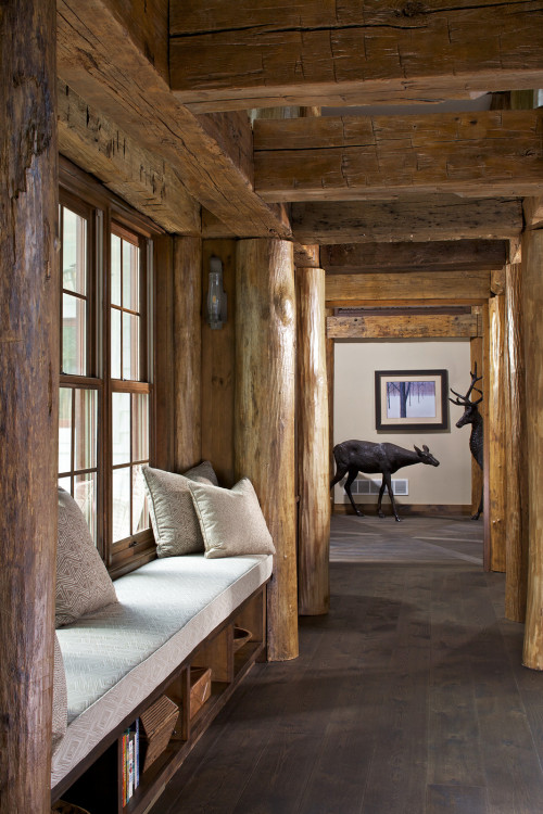 Natural wood beams in hallway with window seat and deer statues