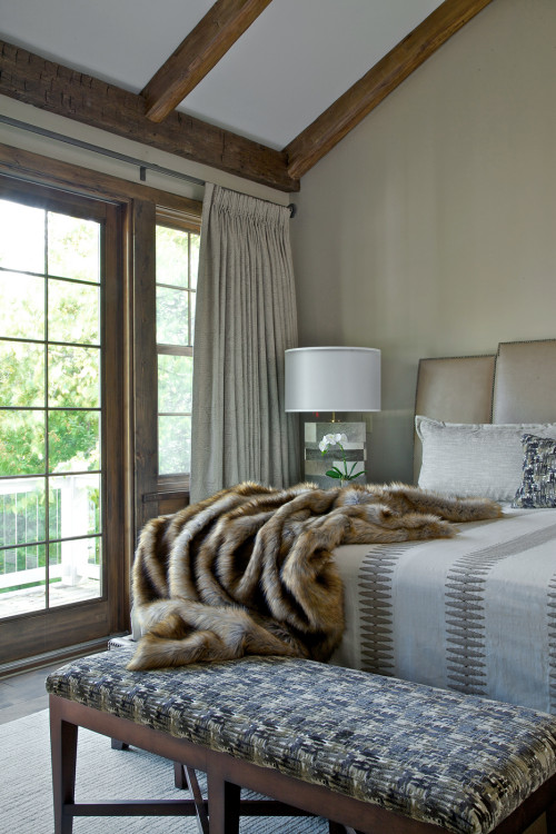 Neutrally decorated master bedroom with faux fur throw on the bed