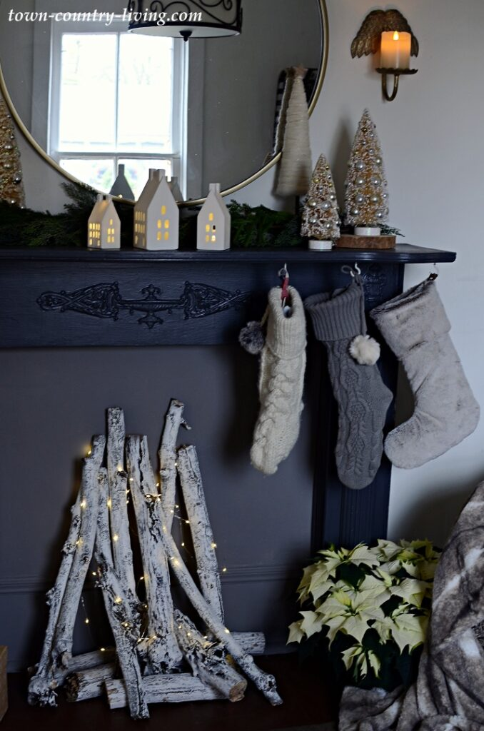 Black Vintage Mantel Decorated for Christmas with Stockings, Greens, and Birch Logs