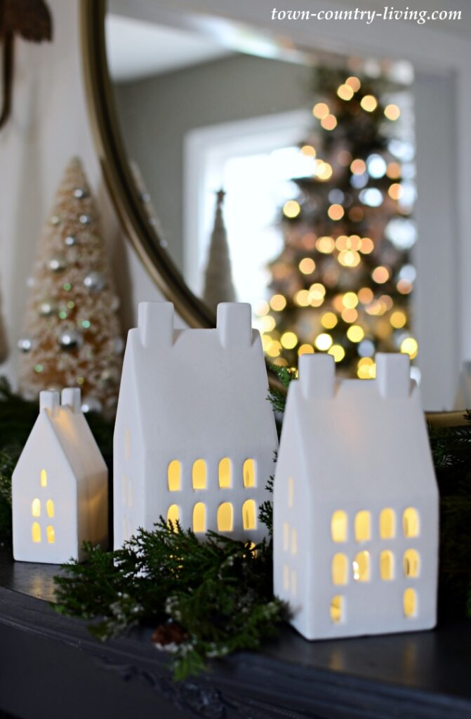 White Ceramic Light-Up Houses and Christmas Greenery on a Black Vintage Mantel