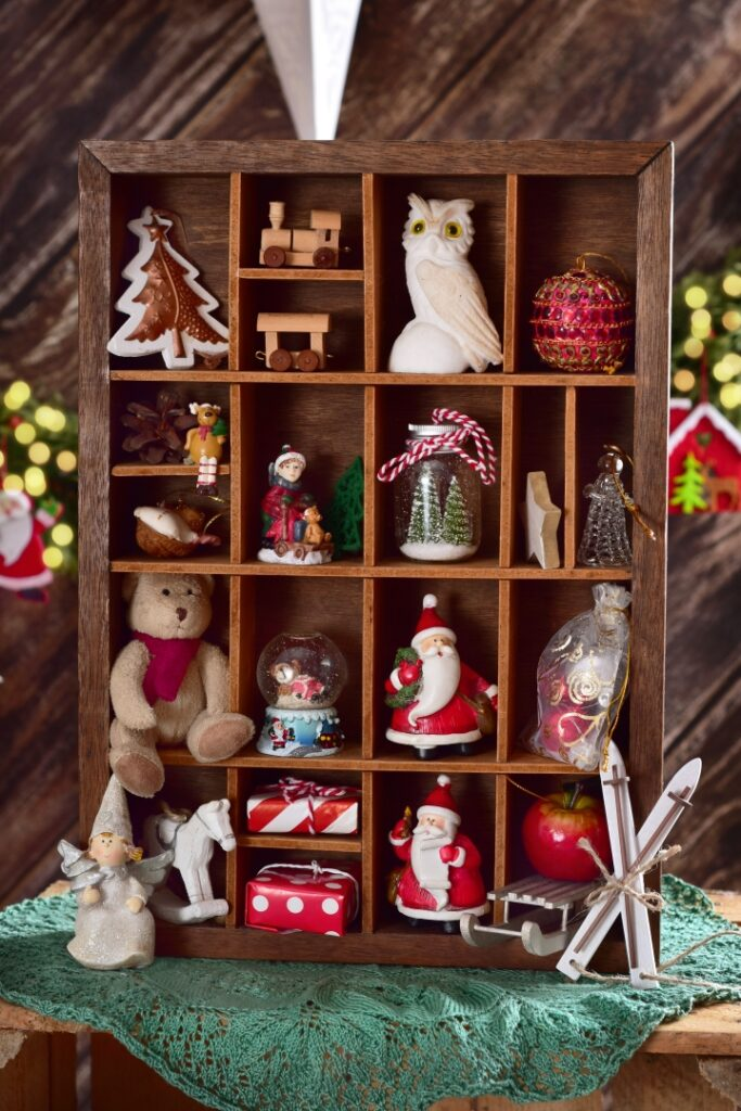 wooden shadow box with collection of Christmas retro style decor ornaments and toys inside
