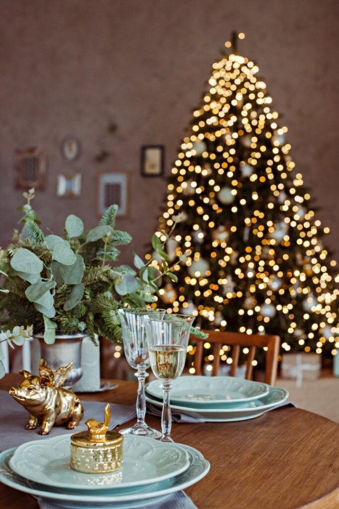 Christmas table setting with gold pig and gift on plate