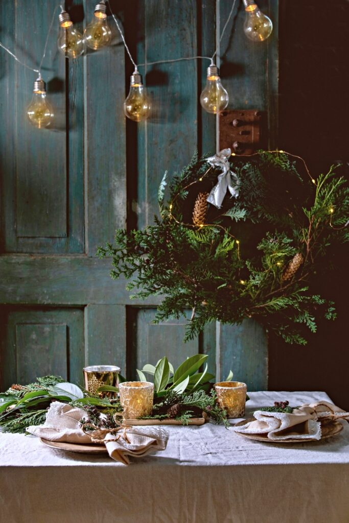 Christmas or New year table setting with empty ceramic plates, napkins, Christmas thuja wreath, luminous garland and burning candles on white tablecloth. Holiday mood