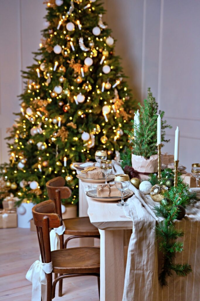 Christmas or New Year festive table setting. The festive wooden dining table is decorated with spruce garland and white candles. Christmas gift on a plate.