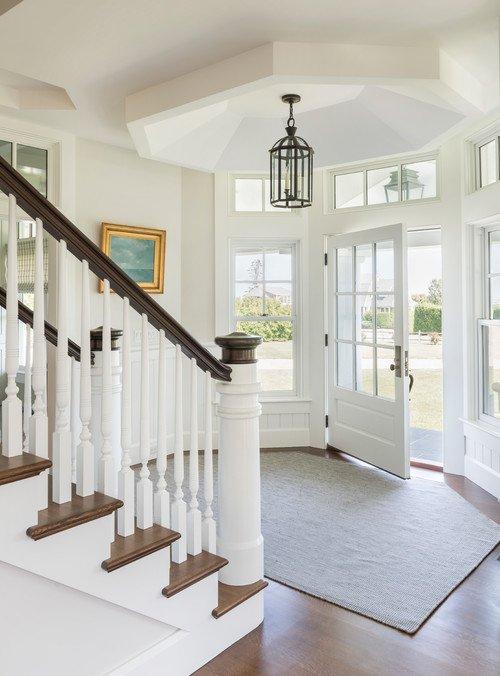 Grand white staircase in entryway of Boston coastal home