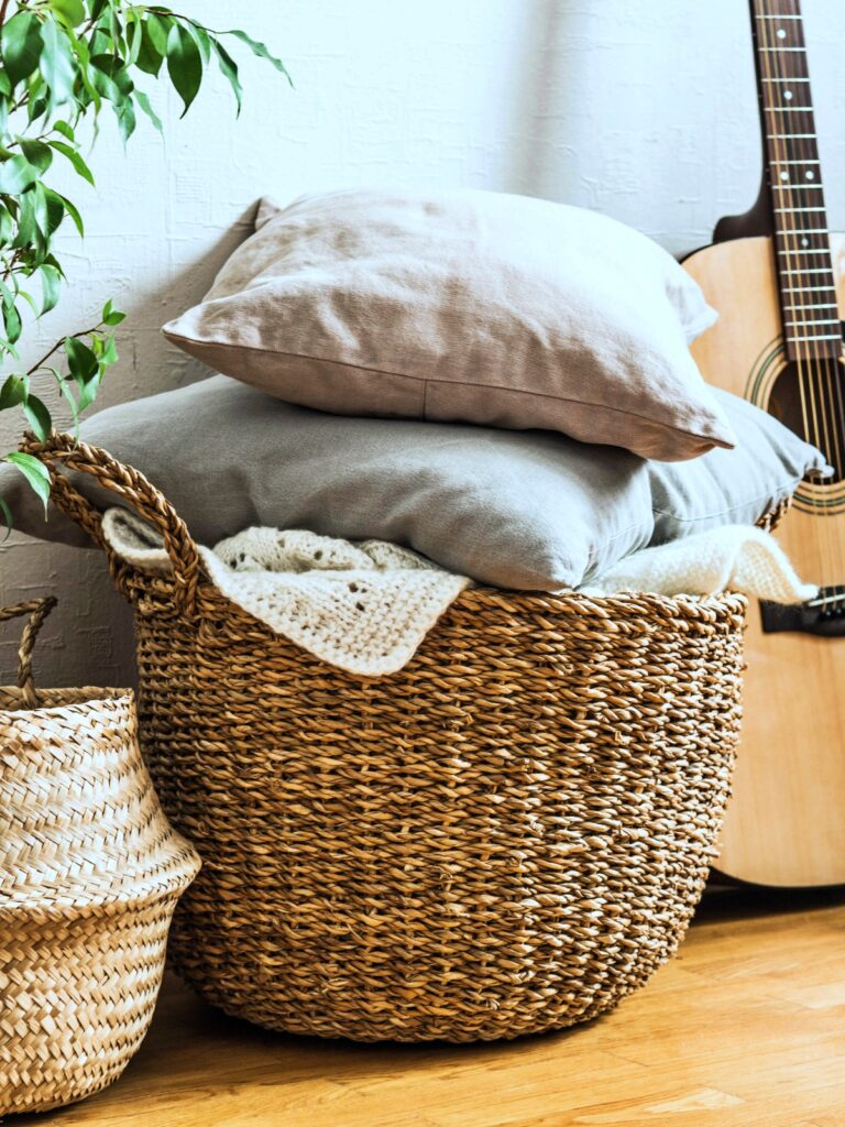 Wicker basket with gray cushions, houseplant and guitar on floor