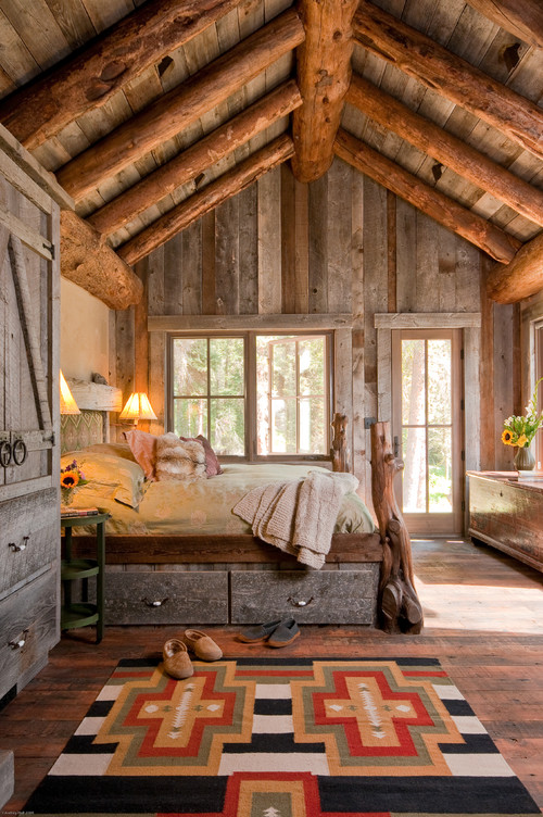 Cabin bedroom with wood vaulted ceiling and views of the evergreens outside