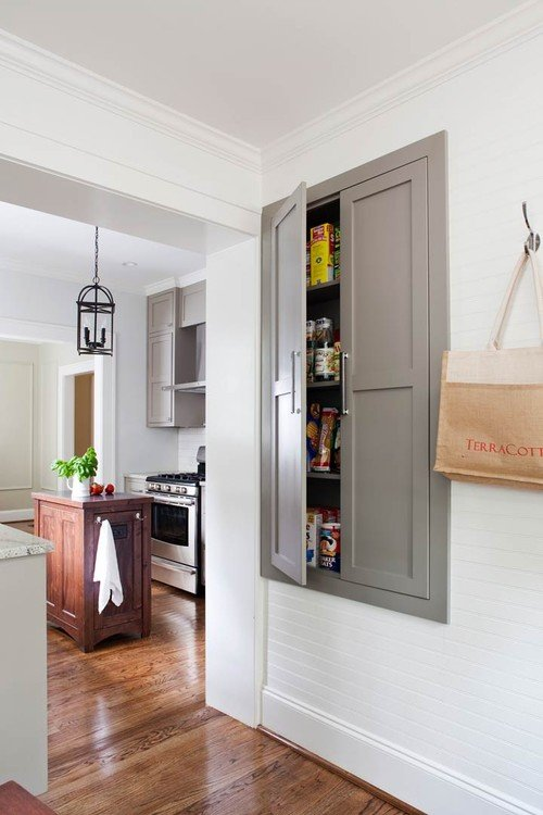 Kitchen pantry built into wall and hallway of charming older home