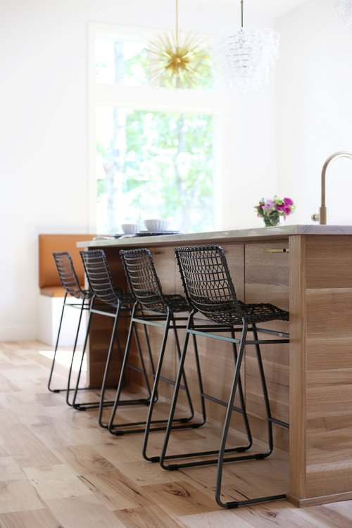 Large kitchen island in transitional kitchen with woven bar stools
