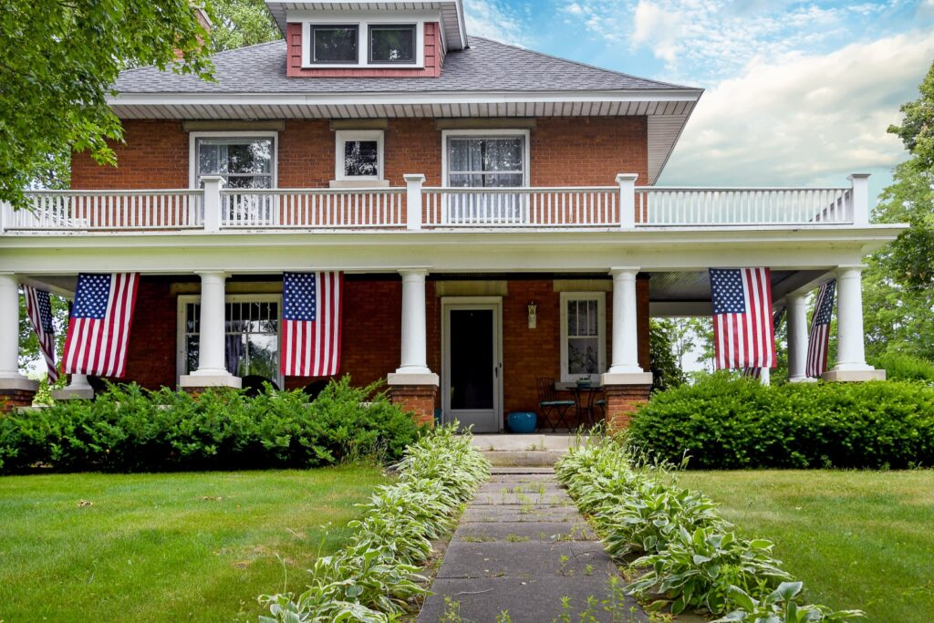 Brick House with Large Front Porch and Trio of Flags
