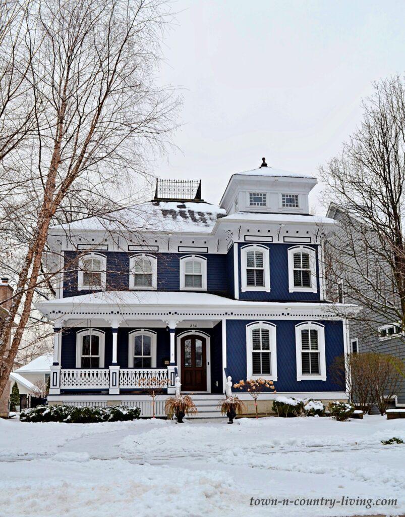 Dark Blue Victorian Home with White Trim on a Winter Day