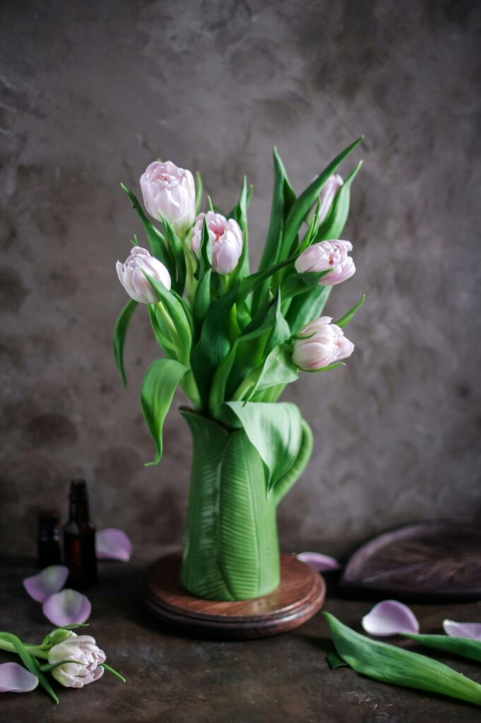 Tulips in vase with green leaf pattern