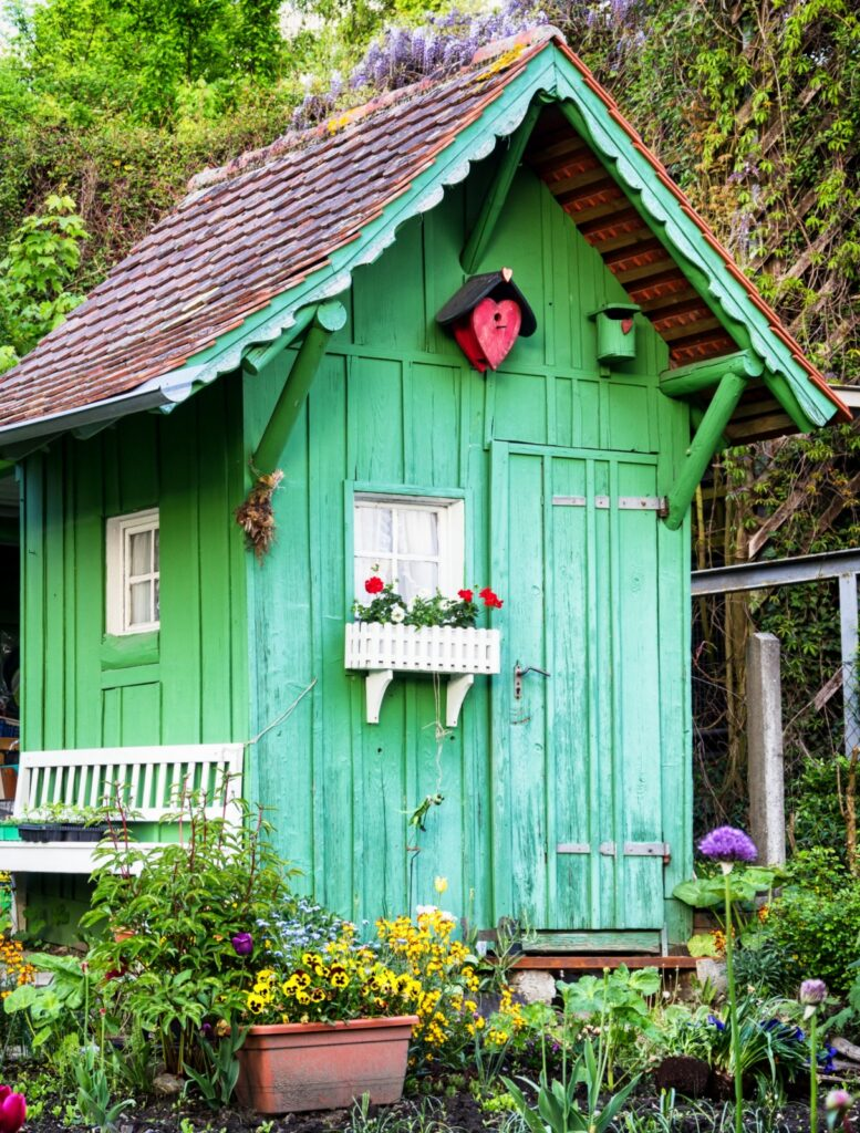 Small green cottage style garden shed