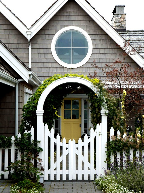 White Picket Fence with Flower Arbor at Gray Cottage with Yellow Door