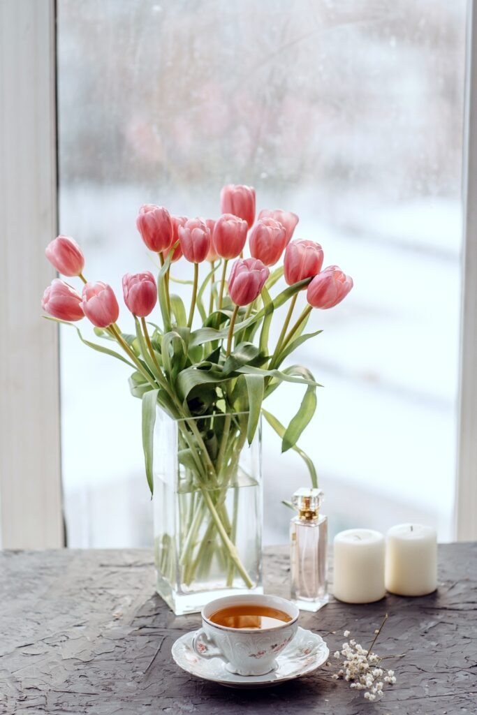 Bouquet of tulips, candles, on a gray table by the window