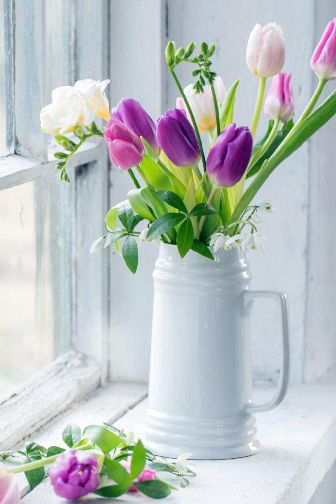 beautiful tulips in jug on old white windowsill