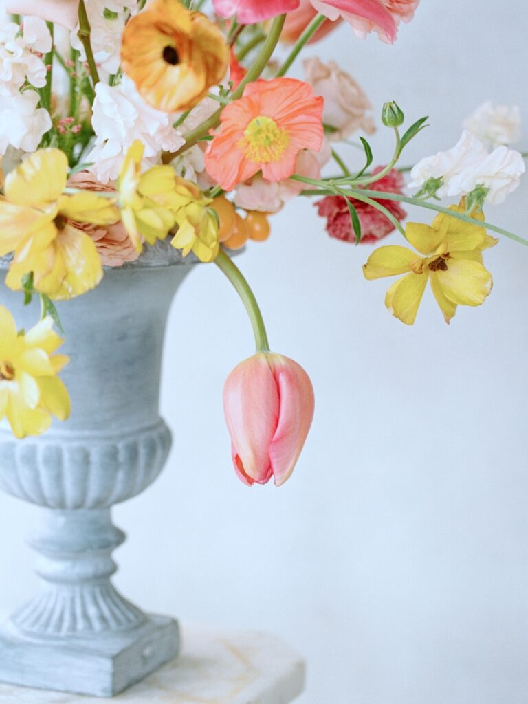 Tulips, poppies, sweet peas in a pink and yellow floral arrangement