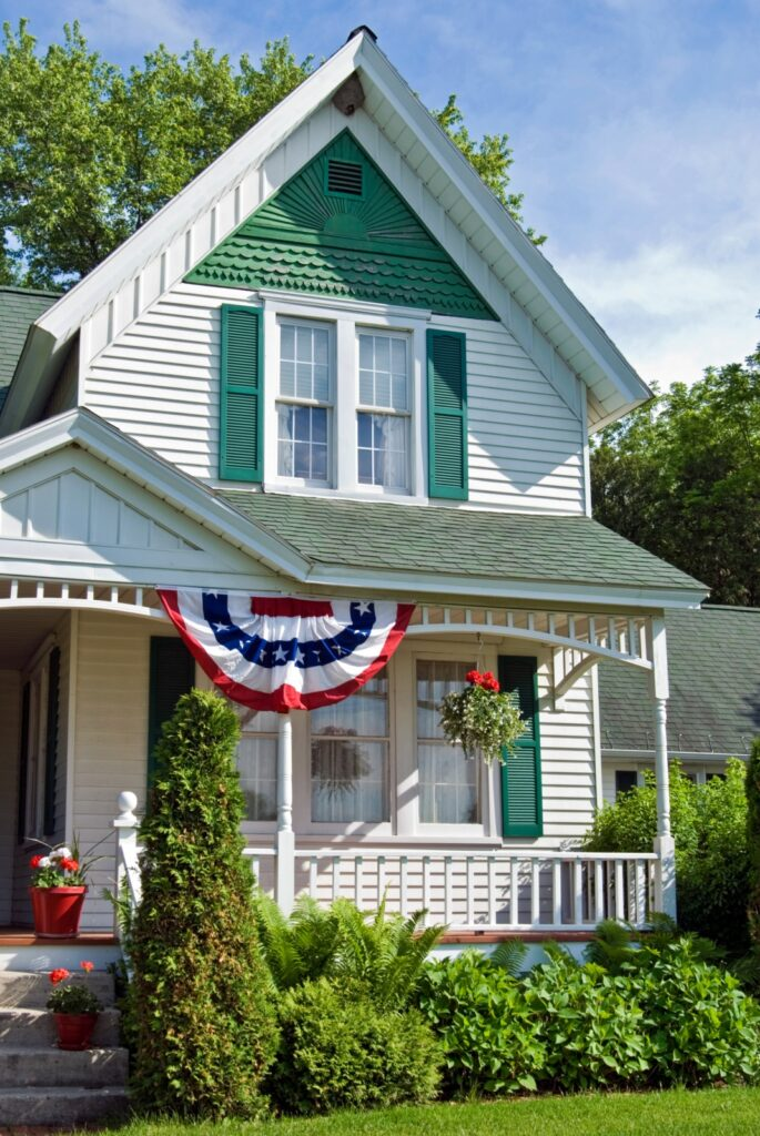 Victorian White and Green Home with Patriotic Bunting on Front Porch