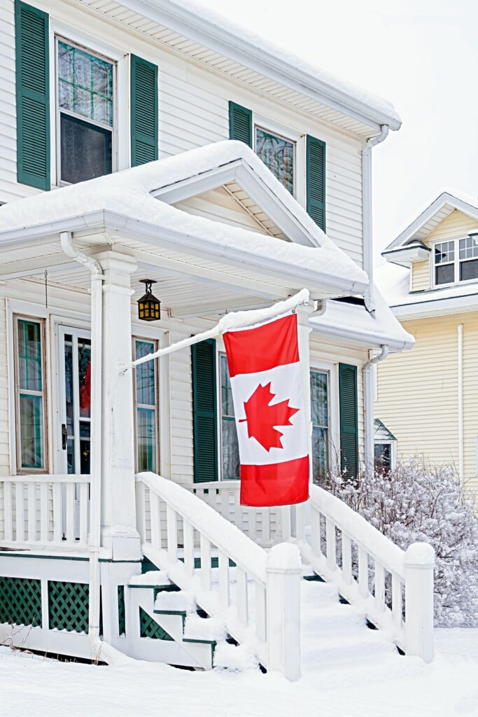 Snowy White House with Green Shutters and Canadian Flag