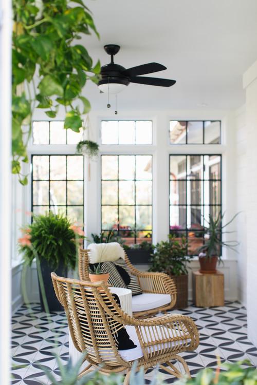 White sun room with rattan furniture in modern farmhouse