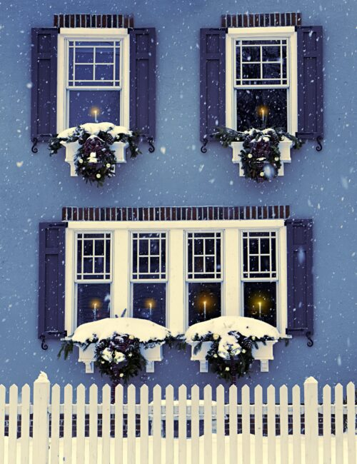 Blue House in Winter with White Picket Fence