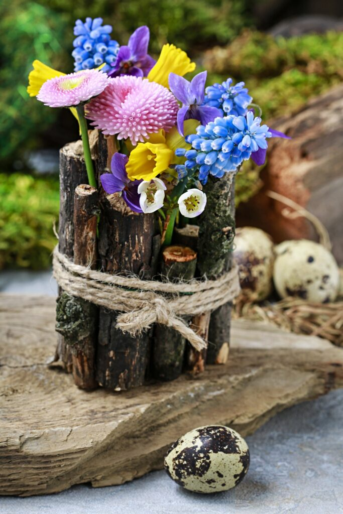 Rustic twig vase with spring flowers - musari, daisy, daffodil, violet
