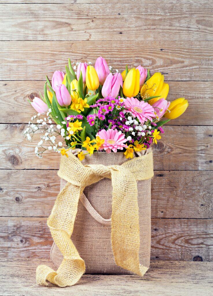 Beautiful spring flowers in burlap bag