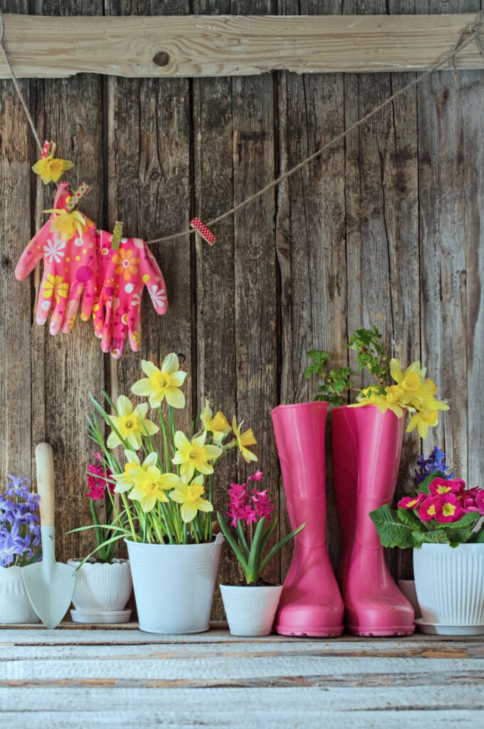 Outdoor Spring Vignette of Pink Rain Boots and Spring Flowers