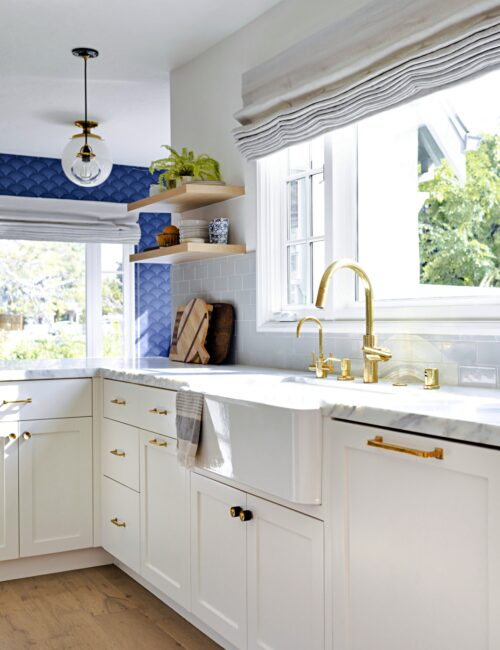 Beach Style Kitchen with White Cabinets and Blue Wallpaper