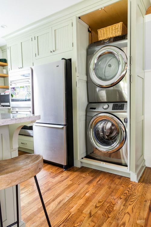 Light green bead board cabinets in classic kitchen with stackable washer and dryer